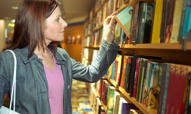B8H3RE Woman shopping in a bookstore