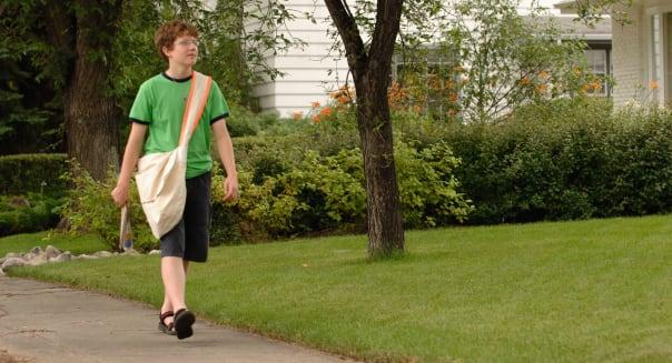 Newspaper boy walking down street, Regina, Saskatchewan