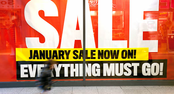 January Sale UK sign shop window and child running, Lion Yard, Cambridge England