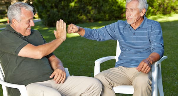 D6P08D Two befriended senior men greeting each other with a youthful gesture fist pump retirement