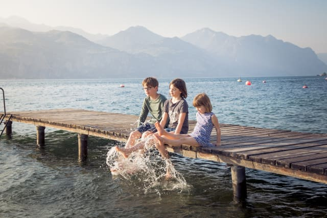 Italy, Brenzone, three children sitting side by side on jetty splashing with water