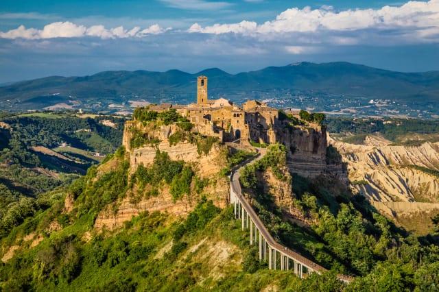 Ancient town of Civita di Bagnoregio with Tiber river valley in golden evening light, Lazio, Italy