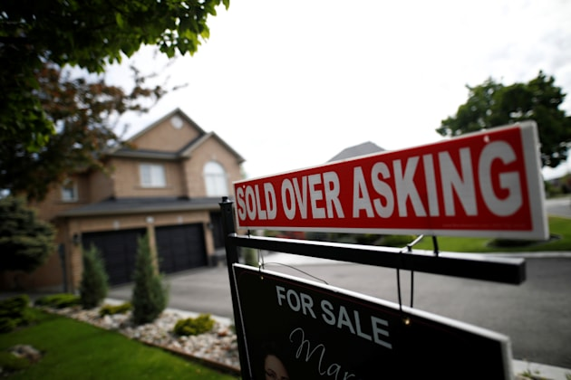 """A real estate sign that reads """"For Sale"""" and """"Sold Above Asking"""" stands in front..."""