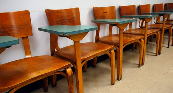 Rows of empty wooden antique desk-chairs with turqouise writing surfaces in an aging classroom.