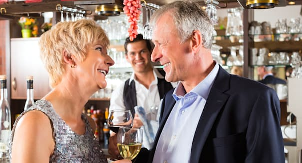 Senior couple in restaurant standing at bar with glass of wine in hand and having fun