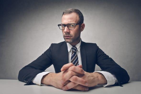 serious businessman sitting at...