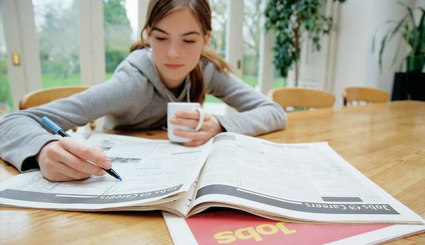 Teenage Girl Sitting Behind a Table Searching for Jobs in a Newspaper