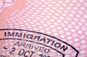 Immigration stamp on a passport page.  Extreme close-up with selective focus. Passport page is gradually blurred with distance.