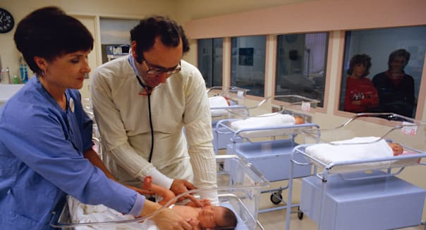 Medical - A pediatrician and nurse examine a newborn infant in a hospital nursery / USA.