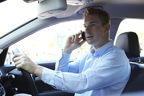 Businessman driving while on phone