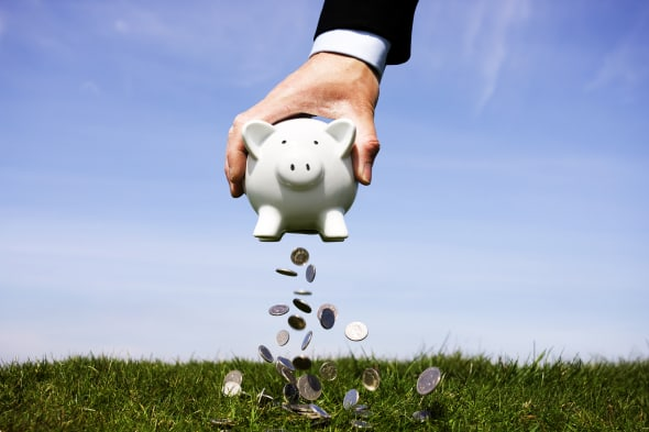 Businessman shaking money out of a piggy bank