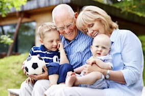 Portrait of happy grandparents with their grandchildren sitting outdoors
