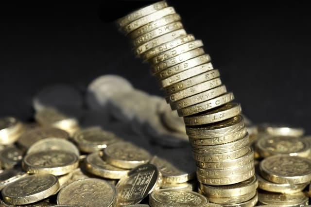 Stack of one pound coins falling over