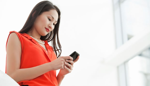 Young businesswoman reading texts on cellphone