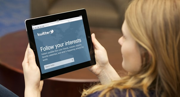 Close up picture of a young woman using Twitter social networking website on an iPad 2
