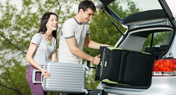 Happy couple going to vacations, loading their car boot with travel suitcases