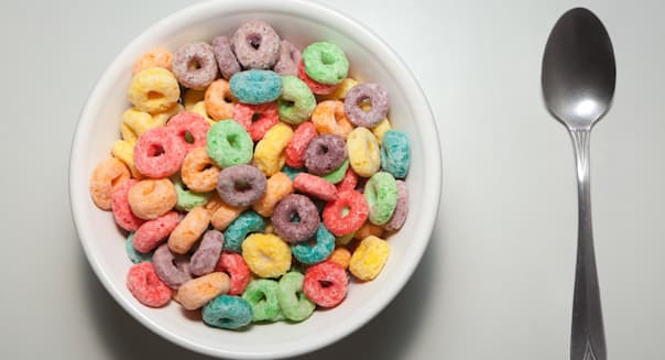 Bowl of colorful breakfast cereal with spoon on plain white background.