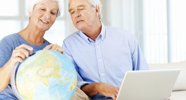 Senior Couple With Laptop And Globe Planning For Retirement