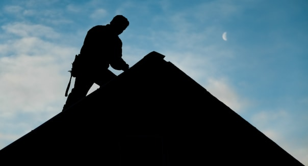 Contractor in Silhouette working on a Roof Top with blue Sky in Background