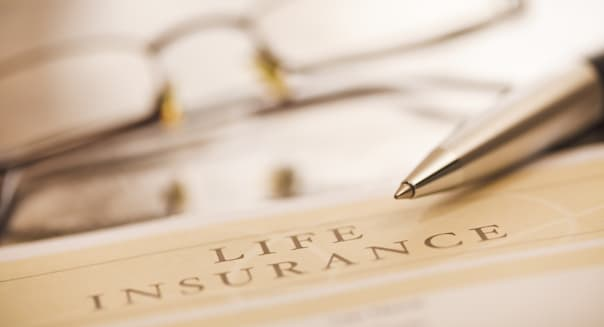'Document entitled life insurance, a pen and glasses on a desk. Close up image. This is an exclusive image and it can only be fo