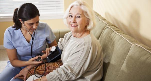Nurse taking senior woman's blood pressure