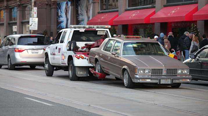 Tow truck  hauling a car on street in downtown Toronto Canada