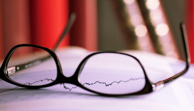 Glasses are laying on a share index.index i going up. Show positive performance. picture is toned