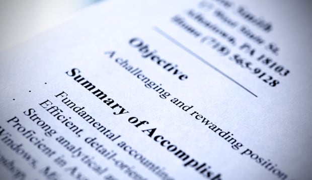 Modern resume close-up. Blue tint with shallow DOF. Tilt view.