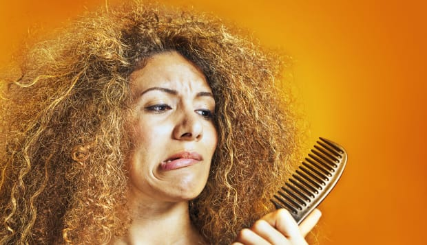 Women with messy hair looking at her hairbrush.