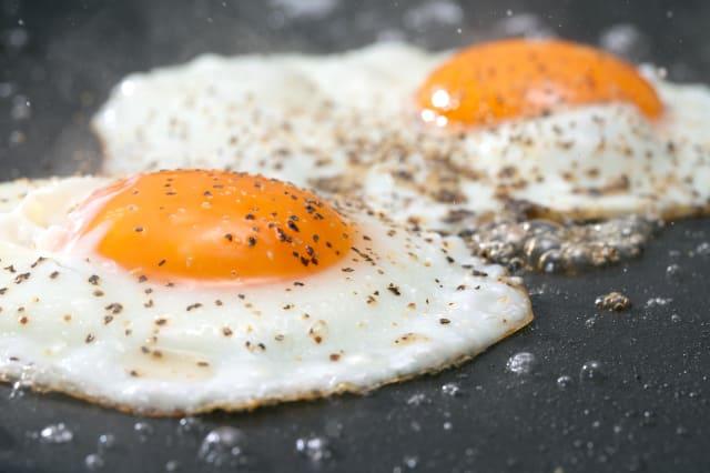 Seasoned eggs frying on a pan.