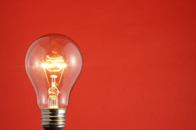 Brightly lit light bulb, against plain red background.