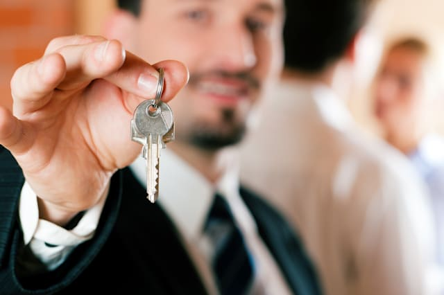 Young couple buying or renting a home or apartment, they are meeting the owner or real estate broker who has the keys; FOCUS on