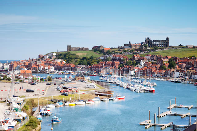 The North Yorkshire seaside town of Whiby, with its Abbey on the headland, the River Esk, and houses clustered around the harbou