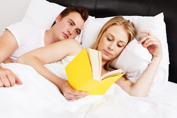 A handsome young couple lie in bed; she's reading; he obviously has something else in mind and is looking unhappy at being given