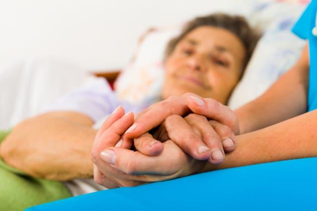 Caring nurse holding kind elderly lady's hands in bed.