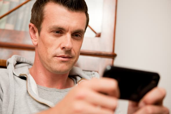 Man using a smart phone at home