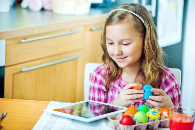 Little girl colors Easter eggs