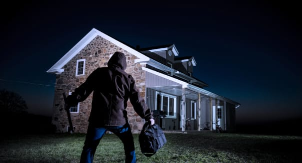 A photograph of a burglar outside a house at night.