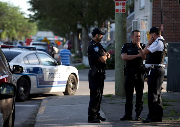 Police investigators talk outside the home of Amor Ftouhi in Montreal on