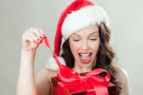 Young brunette woman wearing Santa hat opening Christmas present