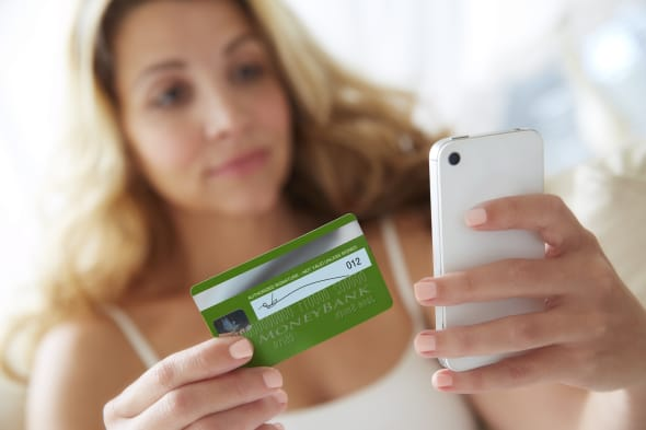 Woman using smart phone mobile device with credit card to make online purchase.