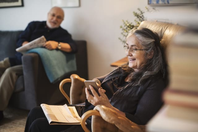Happy senior woman using mobile phone while man sitting on sofa at home