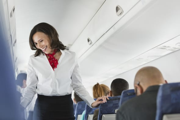 Flight attendant talking to passengers in airplane