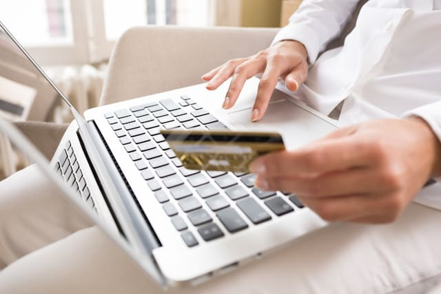 Woman's hands holding a credit card and using laptop for online shopping