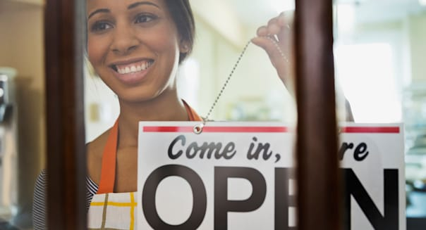 Woman baker hanging 'open' sign on door of bakery