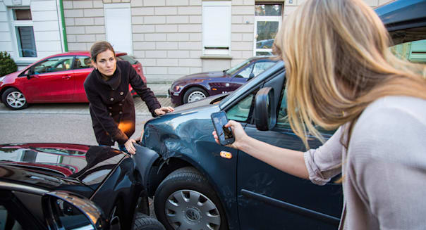 Car accident with minor damage. To woman discus the reason of the car crash, who is guilty.