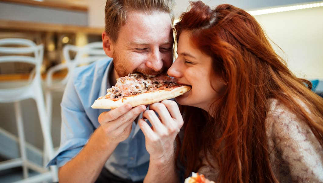 Couple sharing pizza and eating