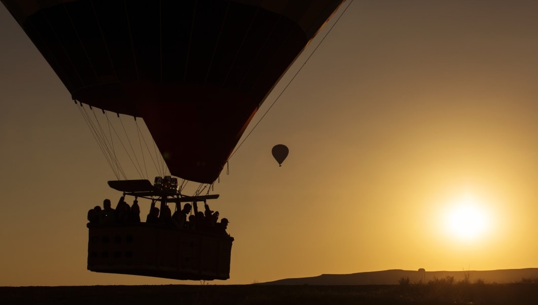 Silhouette of people in balloon on sunrise