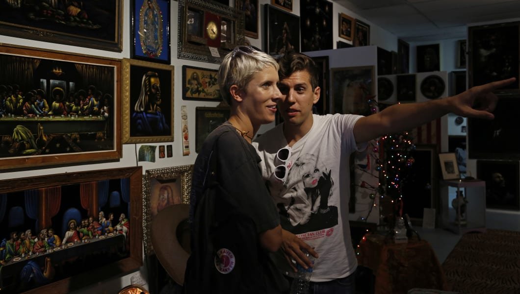 LOS ANGELES, CA - July 13, 2014: Jona Bechtolt, right, points out a painting to Claire Evans, left,