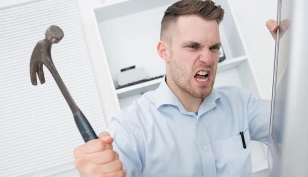 Frustrated man hitting computer monitor with hammer